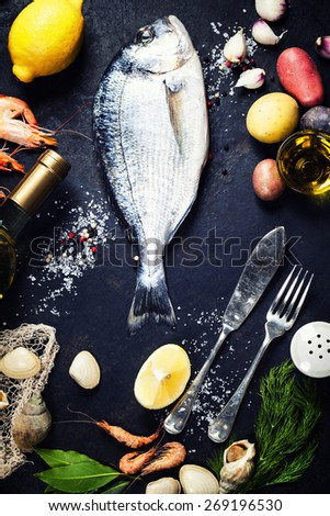 Delicious fresh fish and seafood on dark vintage background. Fish, cockles and  shrimps with aromatic herbs, spices and vegetables - healthy food, diet or cooking concept  - stock photo