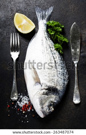 Delicious fresh fish on dark vintage background - stock photo