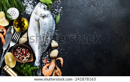 Delicious fresh fish on dark vintage background. Fish with aromatic herbs, spices and vegetables - healthy food, diet or cooking concept
