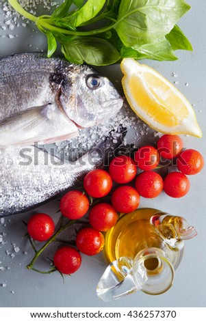 Delicious fresh fish on grey  background. Fish with aromatic herbs, spices and vegetables - healthy food, diet or cooking concept. Gilt-head bream - stock photo