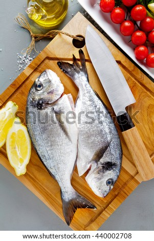 Delicious fresh fish on wooden board , on grey  background. Fish with aromatic herbs, spices and vegetables - healthy food, diet or cooking concept. Gilt-head bream - stock photo