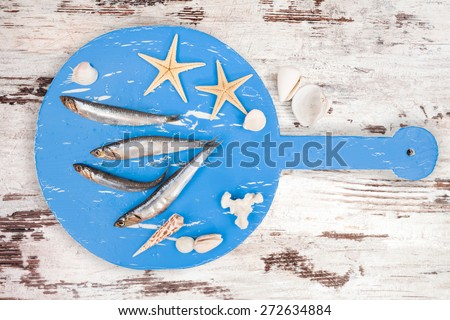 Delicious fresh fish on wooden kitchen board with sea shells on white textured wooden background. Culinary healthy cooking. - stock photo