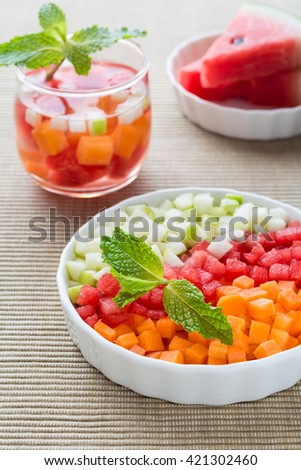 Delicious fresh fruits salad in a white plate on table.
