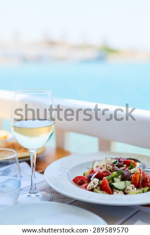 Delicious fresh greek salad and glass of white wine served for lunch at outdoor restaurant - stock photo