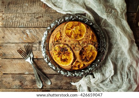 Delicious fresh homemade pie with orange zest, milk, butter, eggs. Decorated with slices of orange on a wooden background. Cake sprinkled with powdered sugar. Decorated with wild flowers
