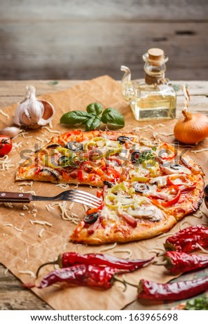 Delicious fresh homemade pizza with ingredients - stock photo