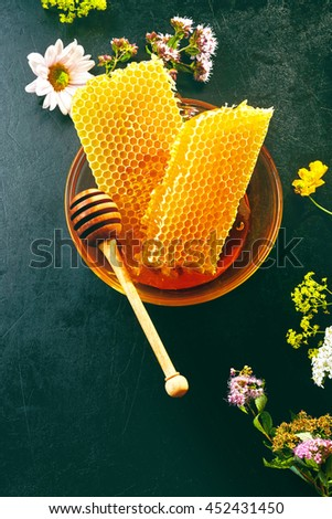 Delicious fresh honeycomb with scattered wildflowers and a wooden honey dipper in a shallow bowl viewed from above on slate with copy space - stock photo