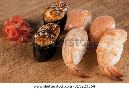 Delicious fresh Japanese sushi rolls . Set with salmon, eel , cheese, california, flying fish roe , red caviar , wasabi mustard Imber . On a wooden board.  Great photos for newspapers, magazines. - stock photo