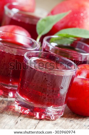 Delicious fresh juice of red and blue sweet plums in a glass on the old wooden background, selective focus