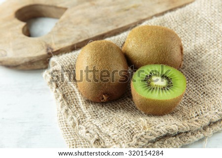 Delicious fresh kiwi fruit on a chopping board - stock photo