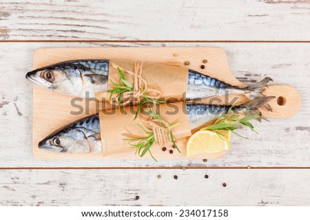 Delicious fresh mackerel fish on wooden kitchen board with lemon, rosemary and colorful peppercorns on white textured wooden background. Culinary healthy cooking. - stock photo