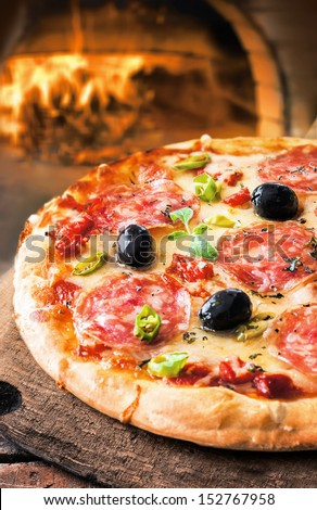 Delicious fresh oven baked spicy salami or pepperoni pizza with melted cheese and olives on a wooden board in front of a roaring fire in a pizza oven at a pizzeria - stock photo