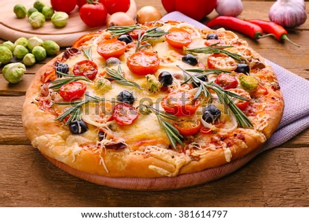 Delicious fresh pizza on wooden table closeup