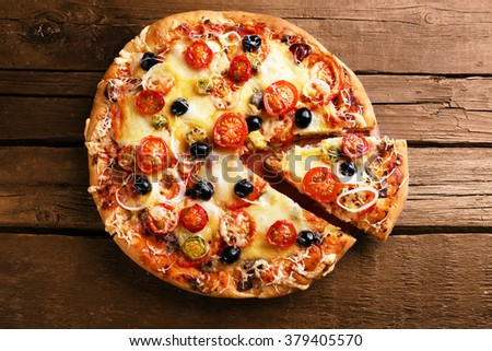 Delicious fresh pizza on wooden table, top view