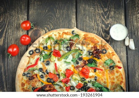 Delicious fresh pizza served on wooden table background - stock photo