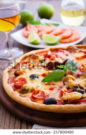Delicious fresh pizza with seafood on wood table - stock photo