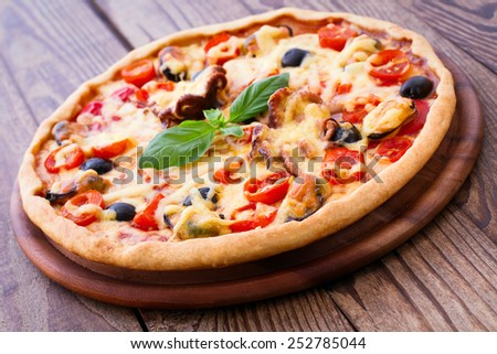 Delicious fresh pizza with seafood on wood table horizontal