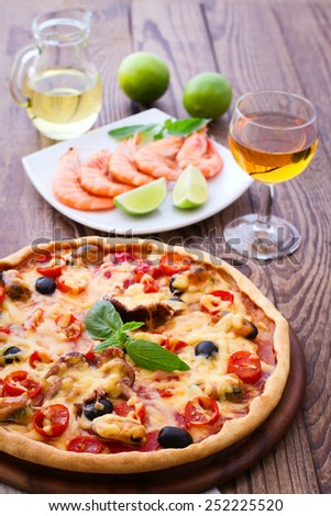 Delicious fresh pizza with seafood on wood table. selective focus, blurry background - stock photo