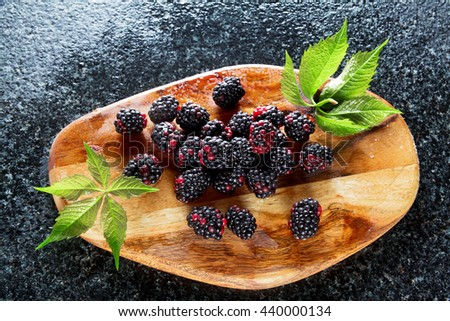 Delicious fresh ripe fruit of Blackberries and green leaves on wooden board on Marble table - stock photo