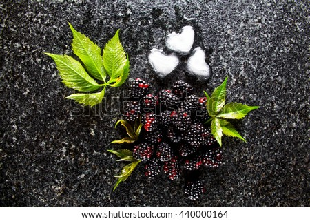 Delicious fresh ripe fruit of Blackberries, cubes of ice and green leaves on a Marble table - stock photo