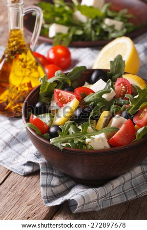 Delicious fresh salad with arugula, feta cheese and tomatoes close-up on a plate, vertical  - stock photo