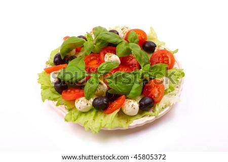 Delicious, fresh salad with basil, mozzarella, olives and tomato. Italian style - stock photo
