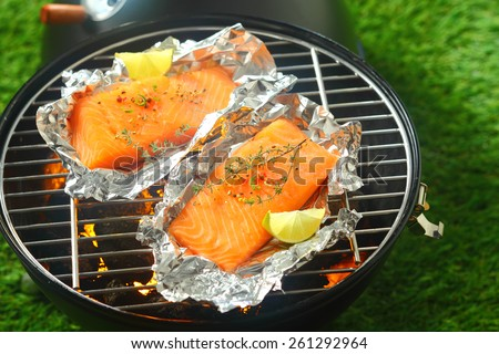 Delicious fresh salmon fillets grilling on an open fire in a portable barbecue lying on tin foil wrappers and flavored with fresh lemon - stock photo