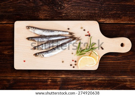 Delicious fresh sardines on wooden kitchen board with lemon, rosemary and colorful peppercorns on wooden background. Culinary healthy cooking. - stock photo