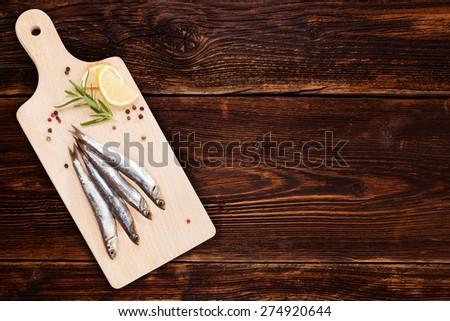 Delicious fresh sardines on wooden kitchen board with lemon, rosemary and colorful peppercorns on wooden background with copy space. Culinary healthy cooking. - stock photo