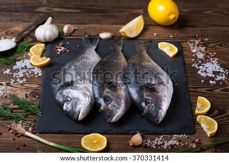 Delicious fresh sea fish on dark wooden background. Healthy food, diet or cooking concept - stock photo