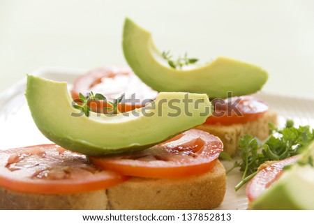 Delicious fresh slice of avocado with tomato and thyme on sliced toasts.