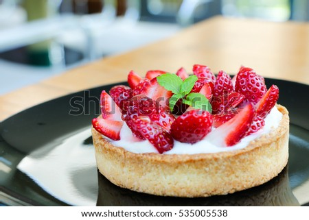 Delicious fresh strawberry tart on black plate