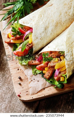 Delicious fresh tortilla wraps with a colorful salad, herb and grilled meat filling served on a wooden board in a fast food restaurant, high angle view - stock photo