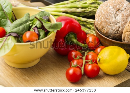 Delicious fresh vegetables for dinner standing ready to prepare on a kitchen counter with ripe cherry tomatoes, red bell pepper, lemon, asparagus spears, baby spinach and brown bread rolls - stock photo
