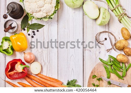 Delicious fresh vegetables forming a frame on white wood with central copy space together with a cutting board, knife and seasoning for cooking - stock photo