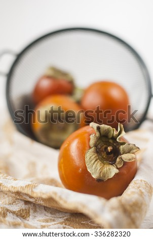 Delicious fresh washed persimmons in a colander. Winter fruits. Selective focus. - stock photo
