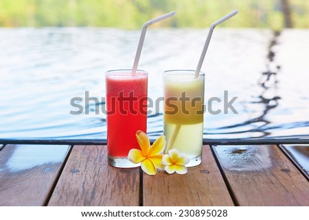 Delicious fresh watermelon and pineapple juices with frangipani flowers near the pool on a tropical Balinese resort  - stock photo