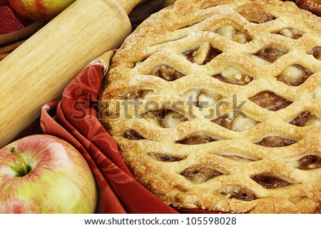 Delicious freshly baked homemade apple pie with rolling pin, fresh apples and cinnamon bark. - stock photo