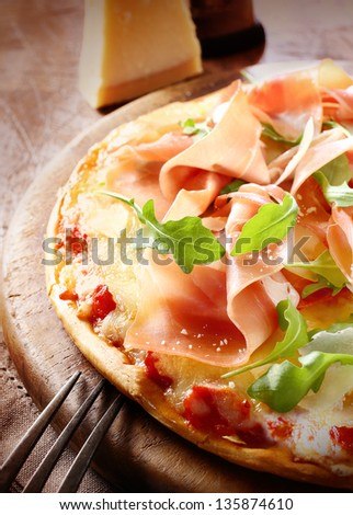 Delicious freshly baked Italian prosciutto ham and rocket pizza with a sprinkling of parmesan cheese served whole on a round wooden board. More pizza at my port. - stock photo