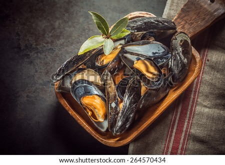 Delicious freshly cooked marinated marine mussels topped with fresh bay leaves served in a rustic wooden bowl for a gourmet seafood appetizer, close up high angle view - stock photo