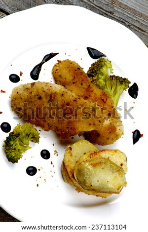 Delicious Fried Chicken Strips in Herb Breading Served with Steamed Broccoli, Roasted Potato Slices and Balsamic Sauce on White Plate Cross Section on Rustic Wooden background - stock photo