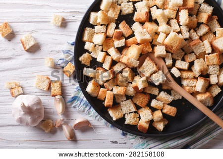 Delicious fried croutons with garlic on a plate close-up. Horizontal top view  - stock photo