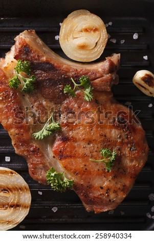 Delicious fried pork steak with onion and garlic in a pan grill macro. vertical top view - stock photo