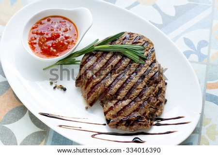 Delicious fried steak with sauce and spices on a white plate. Close-up