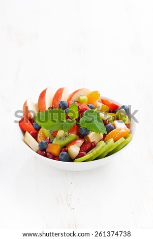 delicious fruit and berry salad in white bowl, vertical, top view - stock photo