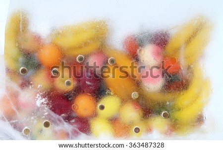 Delicious fruit frozen in a block of ice - stock photo