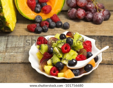 delicious fruit salad with red fruits and fruits background on wood