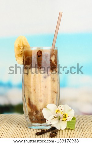 Delicious fruit smoothie on table on blue background