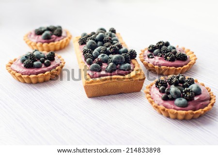Delicious fruit tart made with blackberries and blueberries. Shallow DOF. - stock photo