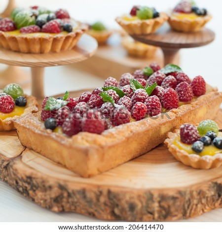 Delicious fruit tart made with raspberries, gooseberries and blueberries on the wooden stand.  Shallow DOF. - stock photo